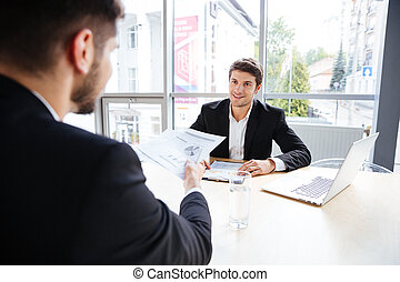 Two happy young businessmen discussing business plan in office