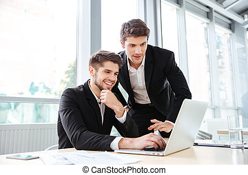 Two cheerful young businessmen using laptop on business...