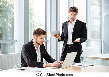 Two handsome young businessmen using laptop and tablet in office