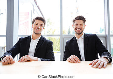 Two cheerful businessmen sitting at the table in office