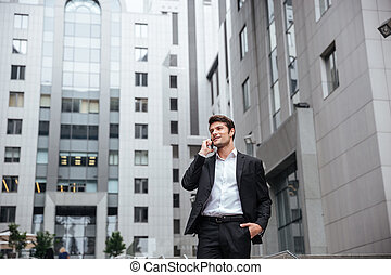 Businessman talking on mobile phone in the city - Smiling...