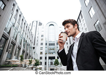 Businessman standing and drinking take away coffee near...