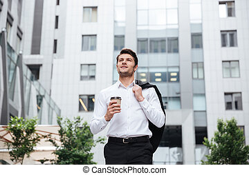 Businessman walking and drinking take away coffee outdoors -...