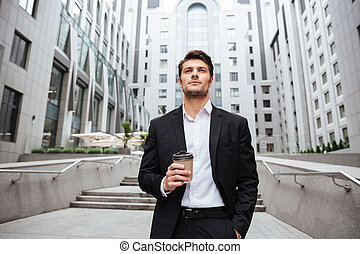 Businessman drinking take away coffee in the city - Serious...