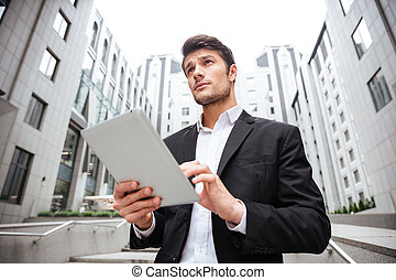 Businessman standing and using tablet near business center -...