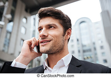 Cheerful attractive young businessman talking on cell phone...