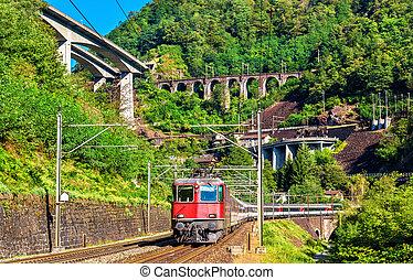 Passenger train is going down the Gotthard pass -...