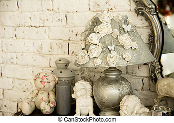 On a shelf reading lamps, ceramic angels and teddy bear...