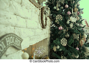Christmas tree about a brick fireplace. Snowflakes on...