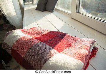 Checkered red plaid on white wooden windowsill.