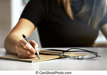 Girl writing in notepad - Girl writing in spiral notepad...