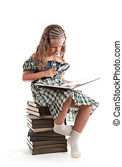 Little girl with magnifying glass reading book