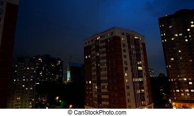 Timelapse of night sky over apartment buildings. Clouds float in the sky, light shines through the windows of houses.