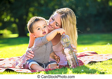 Baby boy grabbing water bottle from mother as they sit on...