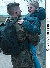 Soldier holding his happy son in his arms