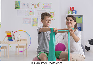 Physiotherapist and boy sitting on a gym ball exercising...