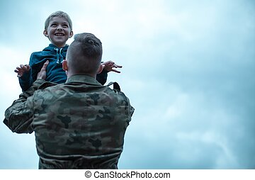 Soldier with his son in his arms - Soldier returning home,...