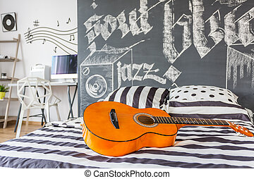 Music inspired bedroom - Shot of a guitar laying on a bed in...