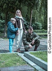 Soldier visiting grave - Soldier with his wife and son...