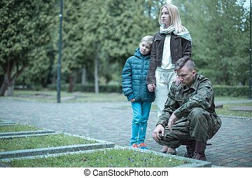 Soldier and his family visiting grave - Photo of a soldier...
