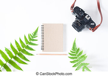 Flat lay of earth tone color notebook, pencil, camera and...