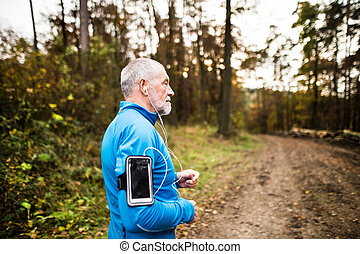 Senior runner in nature with smart phone and earphones. -...