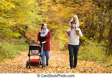 Beautiful young family on a walk in autumn forest. -...