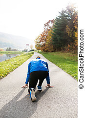 Runner at the lake on asphalt path in steady position -...