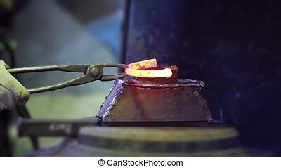 Blacksmith forges a hot horseshoe - Blacksmith forges a...