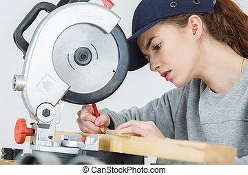 female carpenter marking on wood with pencil in workshop