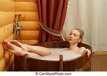 Spa. Beautiful girl taking bath with relaxing oils - Spa....