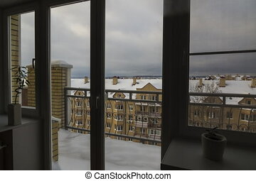 View from the window to snowy rooftops. Day to night...