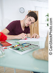 young man drawing pictures in studio
