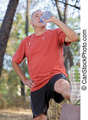 athletic mature man drinking water from a bottle