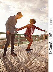 Girl learning to skateboard from boy