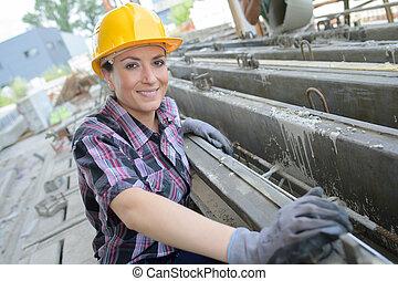 portrait of pretty female worker in a steel mill