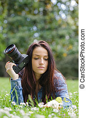 young woman photographer with camera lie down on grass