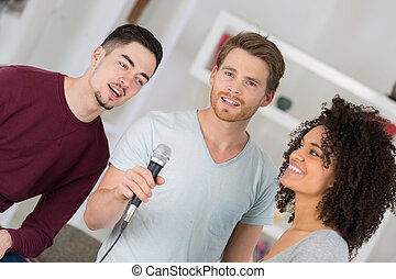 group of friends having fun karaoke singing at home