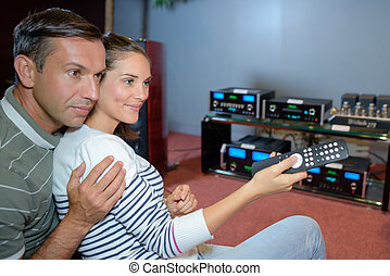 Couple with remote control for sound system