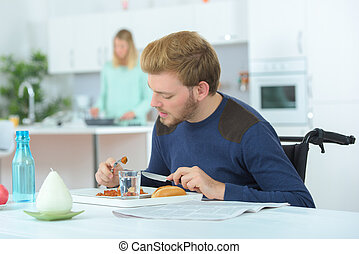 disabled man eating with wife in the background