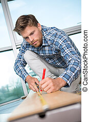 handsome carpenter measuring wood using a tape measure and pencil