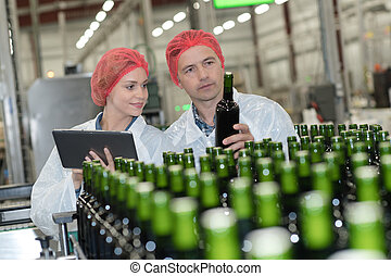 portrait of brewers checking beers at brewery