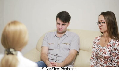 Female psychologist helping worried young couple. happy...