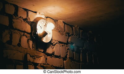 Filament Bulb Lights Up on a Stone Wall - Incandescent Lamp...