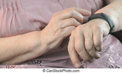 The elderly woman using the smart fitness tracker