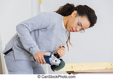 young adult female worker grinding plank with electric...