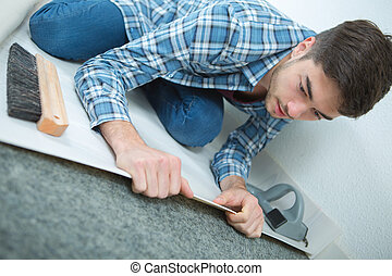 young male unrolling new floor at construction site