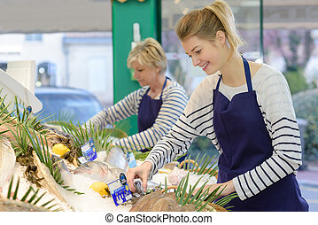 women fishmongers smiling and tidying display