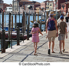 mom and two children walking on the island of Murano near...
