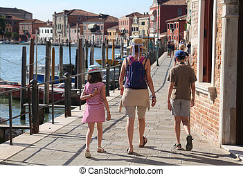 family with mom and two children walking on the island of...